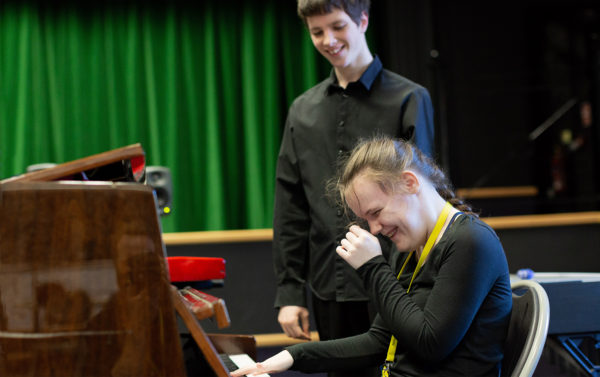 Picture of pianist Ashleigh laughing with Ben cheering her on
